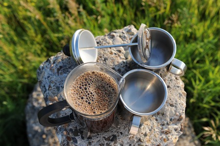Open french press with foam freshly brewed coffee and two cups on stone stand in the open air