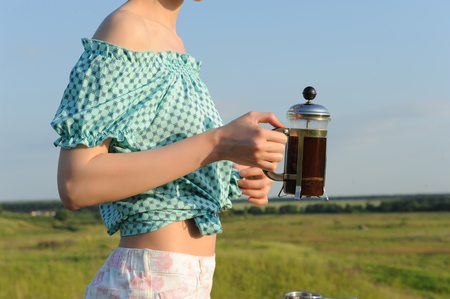 Girl is holding a French press with coffee on the background of herself in nature. Close-up