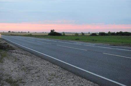 Pink sunset on empty road with markings. Country landscape. Atmosphere of travel