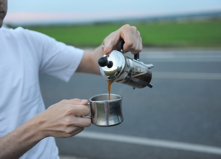 french way: Alternative brewing coffee in a french press on the hood of a car on the side of the road on journey