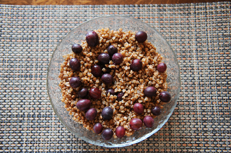 kasha: A large glass bowl of boiled buckwheat with grapes gooseberry on serving napkin
