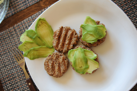 whole wheat toast: Buckwheat biscuits grill and slices of avocado on a white plate. Fork with a wooden handle. Healthy breakfast