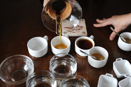 The process of coffee cupping. Coffee is poured into tasting cups