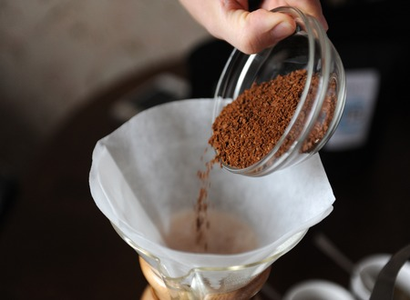 Freshly ground coffee in glass cup is poured into a paper filter for brewing