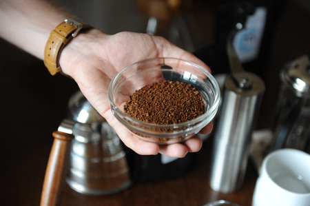 Freshly ground coffee in glass cup in hand, close-up