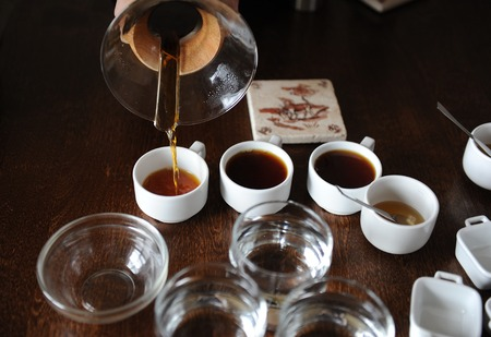Process of coffee cupping. Coffee is poured into tasting cups Stock Photo