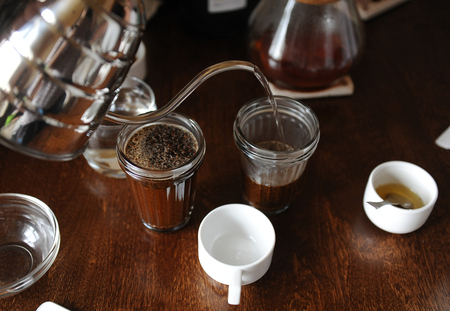 cupping glass cupping: The process of cupping. Coffee is brewed in glass cups Stock Photo