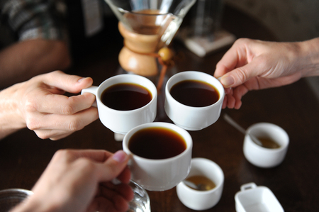 cupping glass cupping: Clink glasses with three cups of coffee on background of coffee items at the tasting Stock Photo