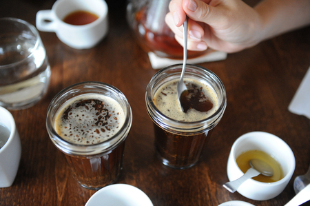 cupping glass cupping: The process of cupping. Tasting freshly brewed coffee with spoons. Coffee accessories on table Stock Photo