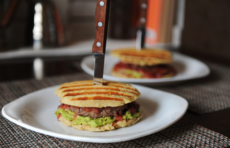 Burger with beef chops, guacamole, cherry sauce, potato bun on the grill. Stabbed with a knife with a wooden handle
