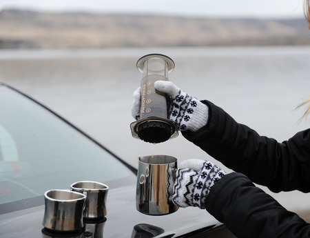 Girl in mittens brewing coffee in aeropress on car trunk by countryside river, winter. Uninhabited monochrome landscape