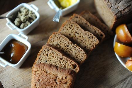 Fresh homemade unleavened bread on the leaven is sliced on wooden board. Serving of breakfast