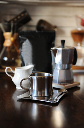 Coffee in moka pot. Stainless steel cup. Devices for manual coffee brewing in the background