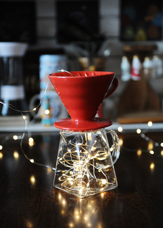 Luminous garland inside in the jug with v60 dripper for coffee brewing. Metaphor creative art visualization of bright taste Фото со стока