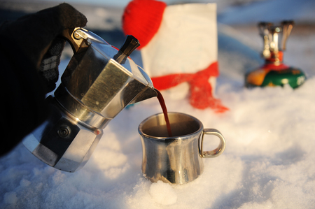 Coffee brewing in moka pot on a gas burner on the car trunk outdoor in winter russian snow landscape.