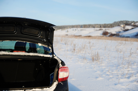 Black car with open trunk on a winter snow Russian country road. Village in the background. Blue sky