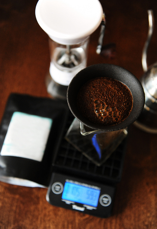 Coffee blooming in porous ceramic paperless dripper filter. Alternative manual brewing. Gooseneck kettle. Electronic scales, manual coffee grinder
