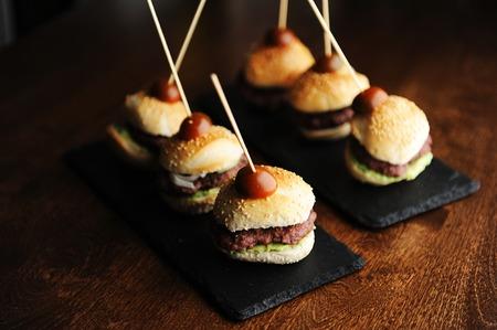 Mini beef burgers on black slate boards. Dark background. Sesame buns