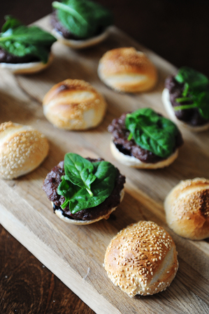 Burger with spinach greens, cutlet, berry sauce and sesame bun. Cooking process. Layout on a wooden board