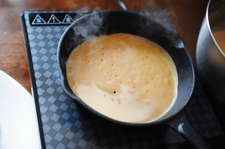 Process of making pancakes. Delicate porous crepes on cast iron skillet. On electric induction cooker stove. Hot steam