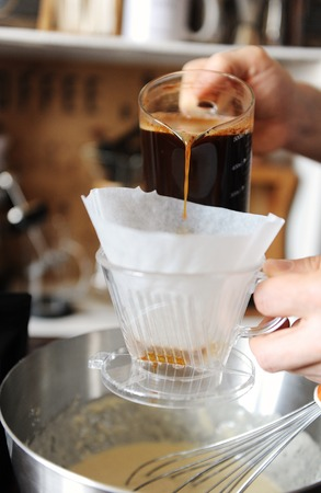 Filtering brewed coffee from a jug through a funnel with a paper filter in bowl with dough. Process of cooking pancakes.