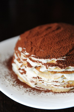 Freshly cooked tiramisu crepe cake dusted with powdery cocoa. White plate, wooden table top view. Half cake close up Фото со стока