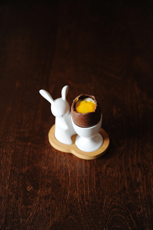 Easter dessert chocolate egg filled with cream and ice cream imitating white and yolk. Served on porcelain holder with Easter bunny. Wooden background, free space