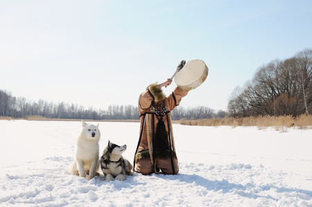 Northern shaman beats tambourine over his head performing a rite calls spring. Husky dogs. Winter landscape