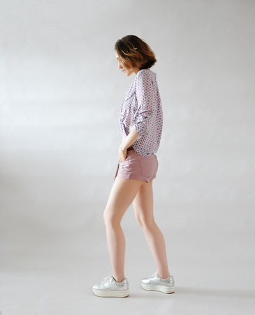 Stylish young girl in shorts on light background. Trendy outfit in pink shades. Sneakers on platform.