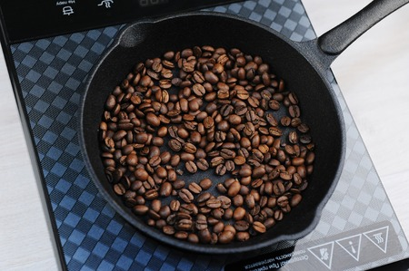 Home roast coffee in a cast iron pan. Induction cooker top view