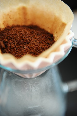 Close up filter coffee bunch brewing origami dripper. Freshly ground coffee. Specialty concept. Alternative brew