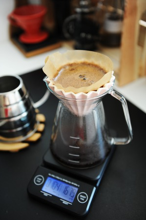 Alternative filter black coffee brew with pink origami dripper. Electronic timer scale. Specialty concept