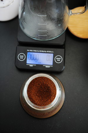 Freshly ground coffee in a manual coffee grinder container top view. Electronic scales with timer