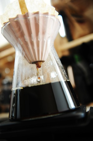 Alternative filter black coffee pour over brewing with pink origami dripper. Specialty concept. Dripping close up
