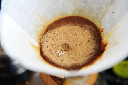 Blooming coffee in paper filter close up. Manual alternative brewing Imagens