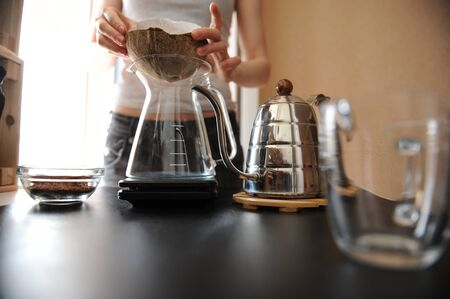 Barista girl brews coffee in an unusual coconut shell purover coconut shell with paper filter Imagens