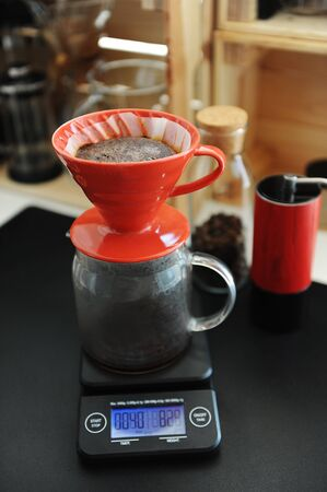 Coffee brewing process. Red ceramic dripper on electronic scale. Blooming. Manual grinder. Specialty concept. Paper filter