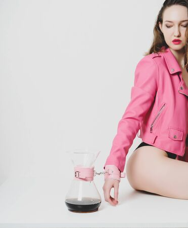 Beautiful girl in pink jacket is fastened with cuffs to coffee jug. Metaphor of passion, affection, caffeine addiction. Standard-Bild