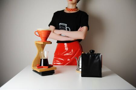 Trendy barista girl brewing filter coffee. Wood drip station. Red patent leather skirt, black t-shirt.