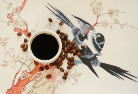 China Yunnan specialty coffee concept. Black coffee in white cup on traditional chinese pattern background. Top view. Catimor