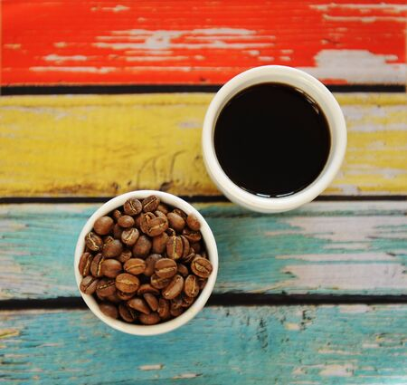 Roasted beans and black coffee in two white cups top view. Colorful red yellow blue striped wooden background