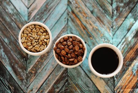 Specialty coffee concept. Green raw coffee beans, roasted coffee beans and black coffee in three white cups on turquoise wooden parquet background top view 스톡 콘텐츠