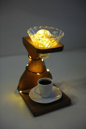 Creative art handmade lamp made of drip coffee stand, v60 dripper and lights. Cup of black coffee in the lower board. Specialty third wave coffee concept