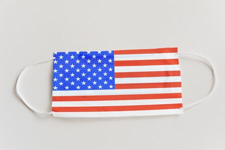 Protective medical mask with the flag of USA. Concept symbol of closing state borders and pandemic control Stock Photo
