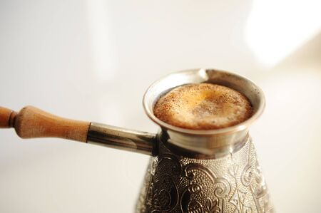 Brewing turkish coffee in cooper cezve. Rising foam close up. White background isolated