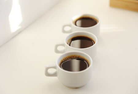 Three white cups with black coffee one after another on white background