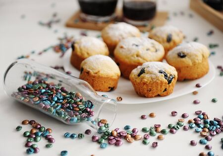 Easter cakes on white plate. Colored coffee beans sprinkled from a bottle Zdjęcie Seryjne