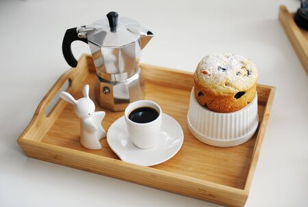 Coffee and cupcake served in wooden bamboo tray. Coffee espresso maker moka pot, white dishes. White background