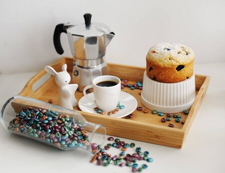 Easter still life with coffee and cake. Served in wooden bamboo tray. Espresso maker moka pot. White dishes, ceramic easter bunny.