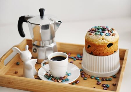 Easter still life. Coffee and cake. Espresso maker moka pot. White dishes, ceramic easter bunny. Colored coffee beans Zdjęcie Seryjne
